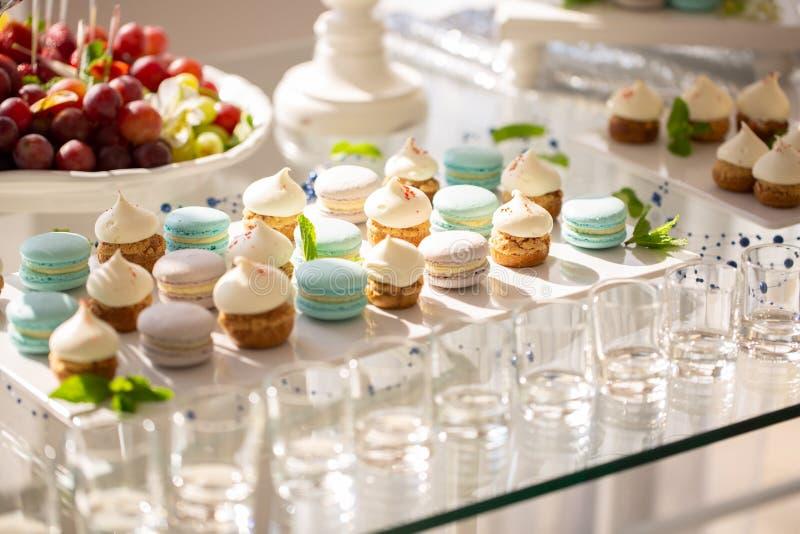Macarrones y magdalenas deliciosos en la tabla en la recepción nupcial Barra de caramelo dulces coloridos sabrosos para los event foto de archivo