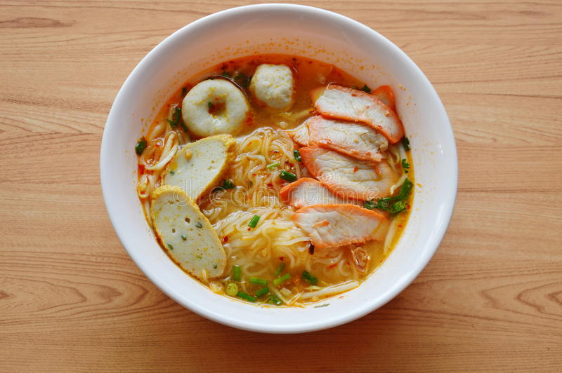 Macarronete de arroz com bola de peixes e carne de porco vermelha do assado na sopa picante fotos de stock royalty free