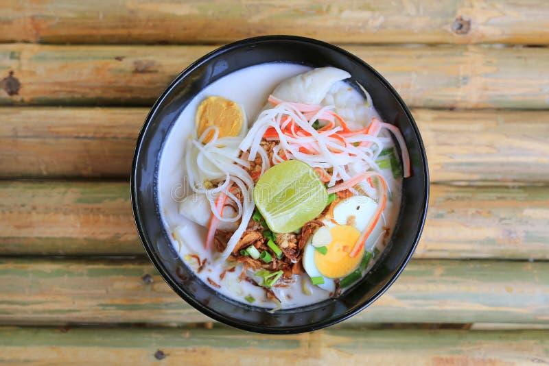 Macarronete na sopa do leite de coco na bacia na tabela de madeira de bambu Alimento tailand?s da fus?o Vista superior fotos de stock