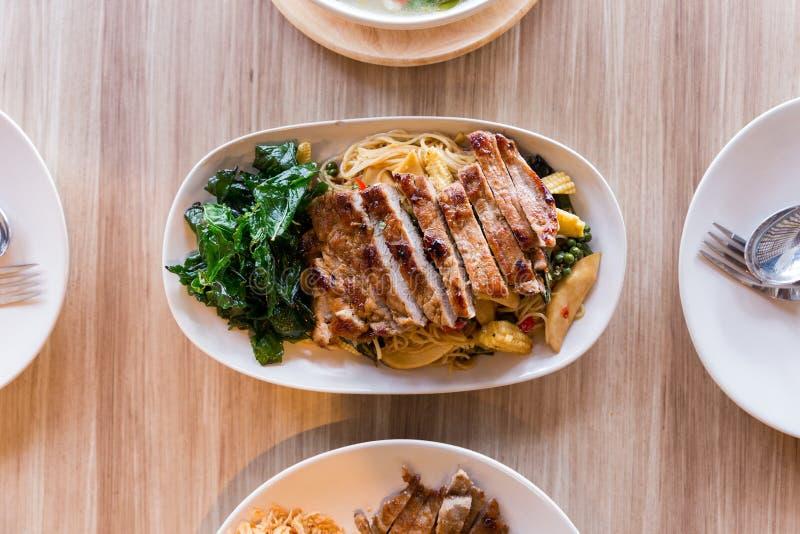 Macarronetes bêbados: O macarronete de ovo frito picante com manjericão e pimenta serviu com carne de porco grelhada foto de stock