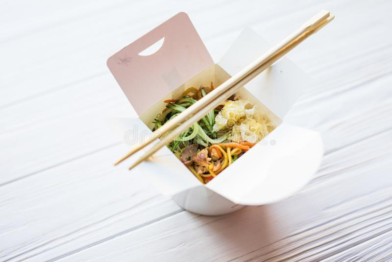 Macarronetes chineses na caixa afastada no fundo de madeira Alimento foto de stock
