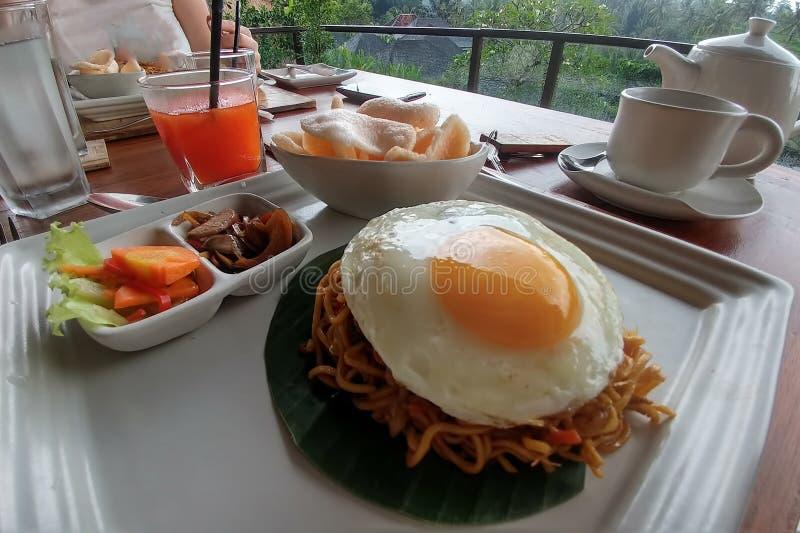 Macarronetes com o ovo frito na folha e na placa Perto dos vegetais na bacia na tabela de madeira Ar livre do café da manhã do ve imagem de stock