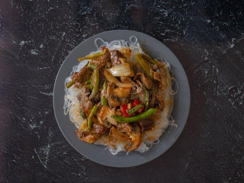 Macarronetes de arroz asiáticos do estilo com Angus Beef com as cebolas pimentão e cogumelos vermelhos dos feijões verdes foto de stock