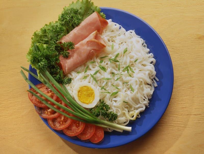 Macarronetes de arroz com bacon cortado, presunto em uma placa azul imagens de stock royalty free