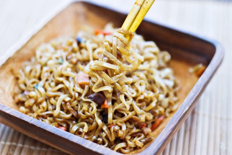 Macarronetes de Ramen envolvidos em torno dos chopsticks imagem de stock royalty free