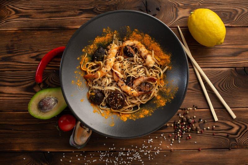 macarronetes do Singapura-estilo com cogumelos e camar?es de shiitake em uma placa preta em um fundo de madeira fotos de stock royalty free