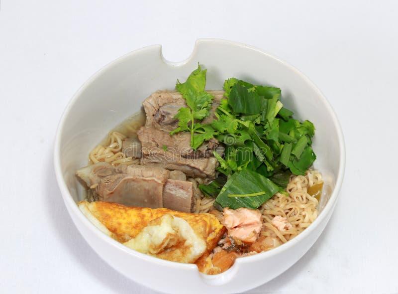 Macarronetes imediatos fervidos com rasgo da carne de porco, ovo frito, carne de peixes e o vegetal verde na bacia branca fotografia de stock