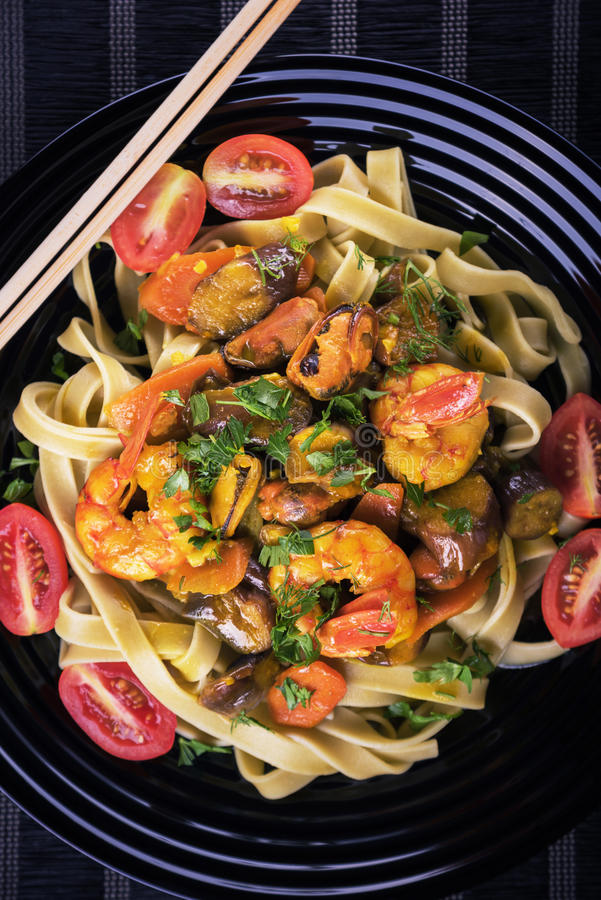 Macarronetes tailandeses saborosos com camarão e marisco e vegetais no prato preto Vista superior fotografia de stock royalty free
