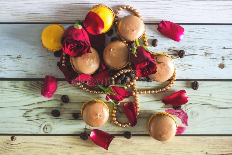 Macaruns con le rose rosse ed il caffè immagine stock