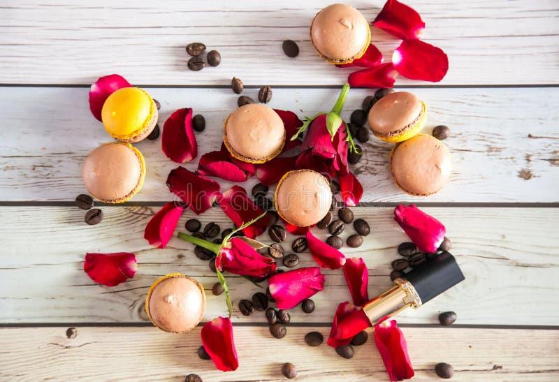 Macaruns français avec les roses rouges et le café photographie stock libre de droits