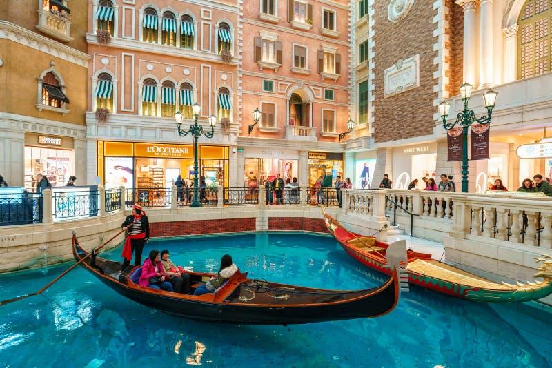 MACAU, CHINA - JANUARY 24, 2016: The Venetian Macau Resort Hotel interior view. Gondolier rides tourists on a gondola along the mock Venetian canal. (Macau is stock photography
