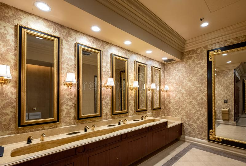 Macau, China - May 05 2018 : Luxury modern wash basin rows with lamp lighting and mirror sorted stock photography