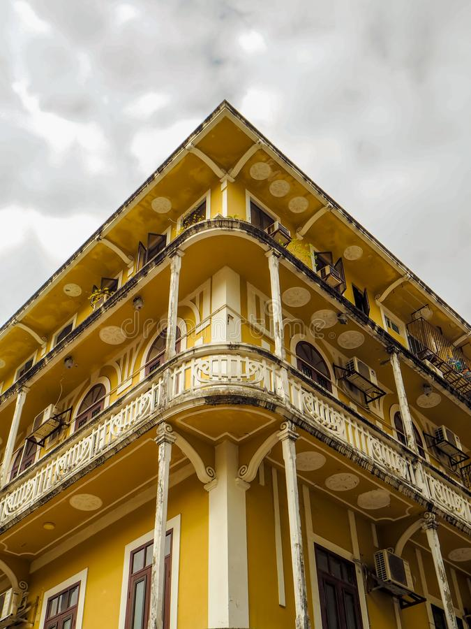MACAU, CHINA - NOVEMBER 2018: Old yellow residential building in the city center with Portuguese and Macanese features. MACAU,CHINA - NOVEMBER 2018: Old yellow stock photo
