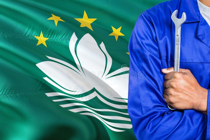 Macau Mechanic in blue uniform is holding wrench against waving Macao flag background. Crossed arms technician royalty free stock image