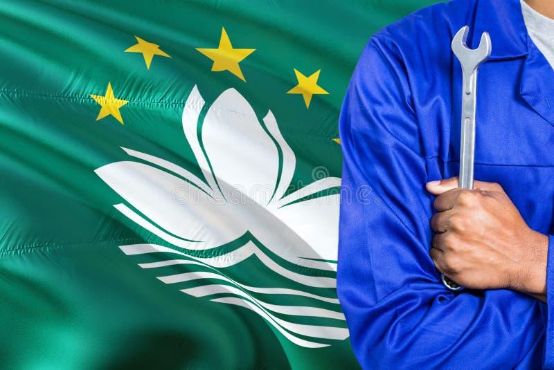 Macau mechanik w błękita mundurze trzyma wyrwanie przeciw machać Macao chorągwianego tło Krzyżujący ręka technik obraz royalty free