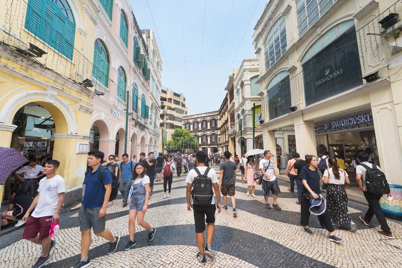 People stroll downtown Macau. MACAU - SEPTEMBER 16, 2017: Lots of people stroll downtown Macau, a major resort city and the top destination for gambling tourism royalty free stock photography