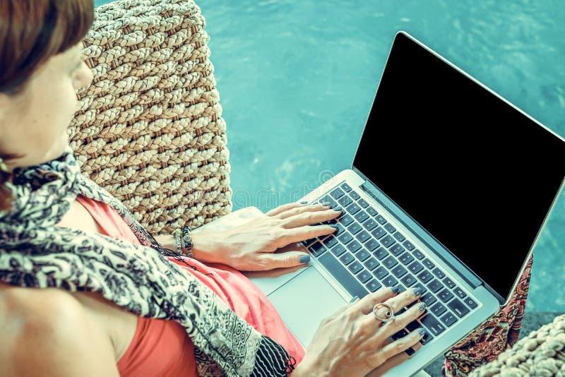 Γυναίκα που φορά τη ρόδινη κορυφή με Macbook στην περιτύλιξη στοκ εικόνες