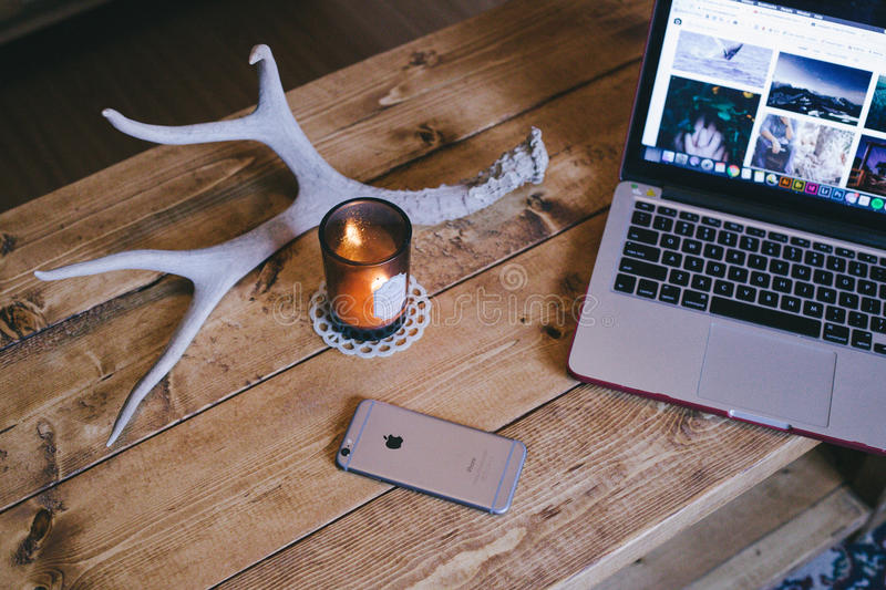 Macbook Pro Beside Brown Glass Candle Holder And Space Gray Iphone 6 On Brown Wooden Table Free Public Domain Cc0 Image