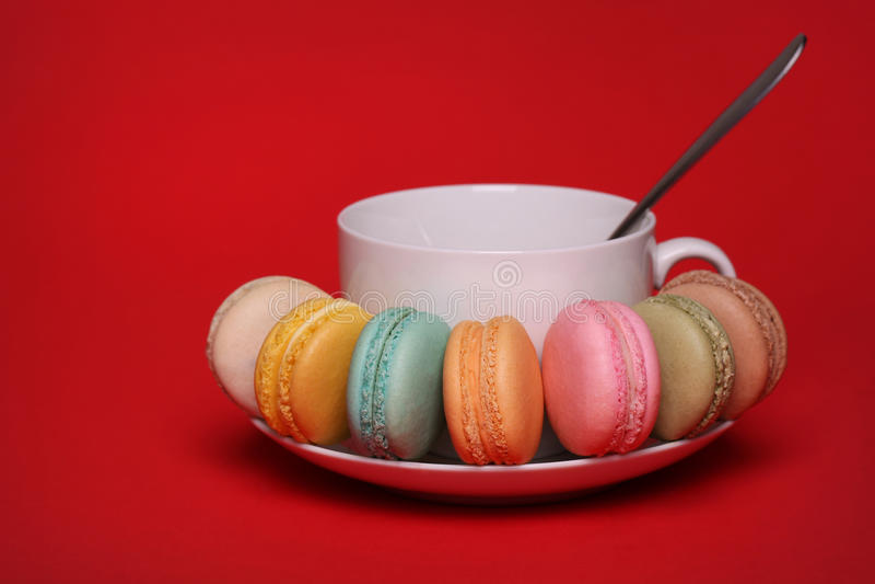 Maccherone francese variopinto con la tazza di tè sopra rosso fotografia stock libera da diritti