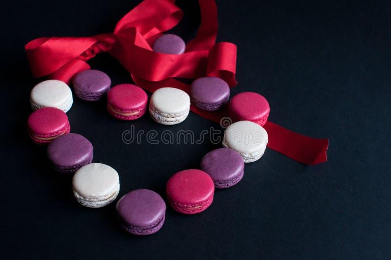 Maccherone presentato su un fondo nero sotto forma di cuore con il nastro rosso Biscotti di mandorla variopinti, colori pastelli  fotografia stock libera da diritti