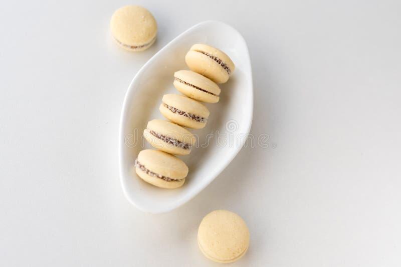 Maccheroni bianchi della vaniglia su fondo di legno Alfajores argentini deliziosi dei biscotti con crema sul piatto Vista superio fotografia stock