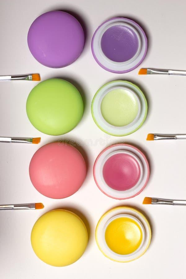 Maccheroni cosmetici che si trovano nella fila, balsami, fondo bianco, spazzole del labbro immagini stock