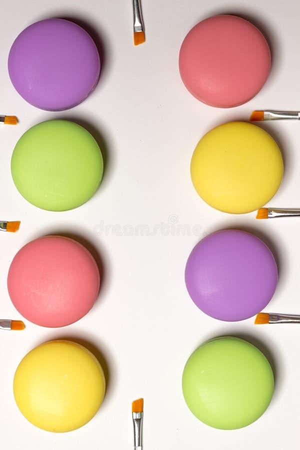 Maccheroni cosmetici che si trovano nella fila, balsami, fondo bianco, spazzole del labbro fotografia stock