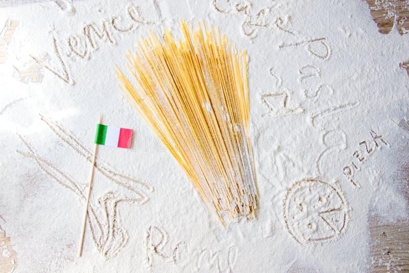 Maccheroni crudi degli spaghetti della pasta e bandiera italiana sulla tavola floured Parole Venezia, Roma e pasta scritte in far fotografia stock