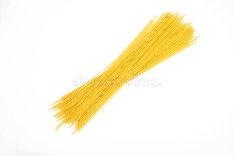Maccheroni crudi degli spaghetti della pasta isolati su fondo bianco immagini stock