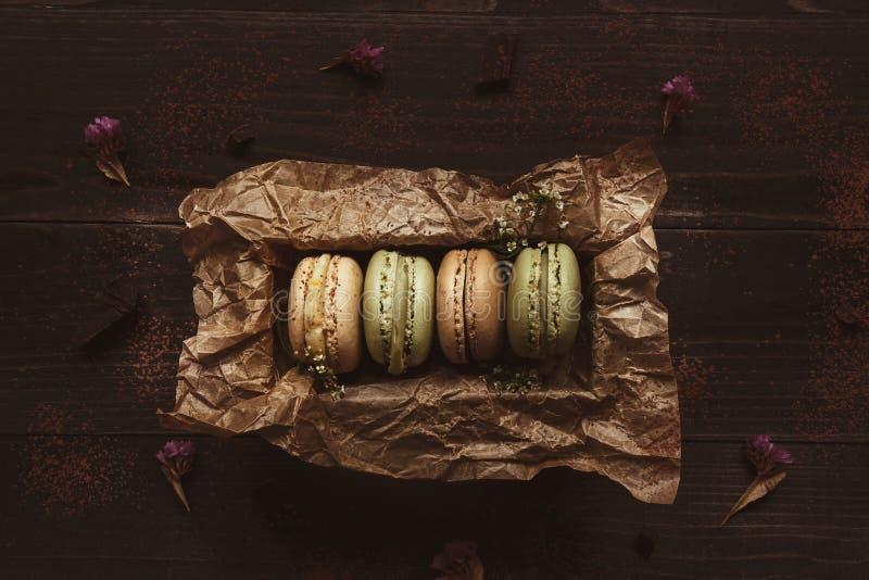 Maccheroni deliziosi in contenitore di regalo sulla tavola di legno, vista superiore fotografia stock