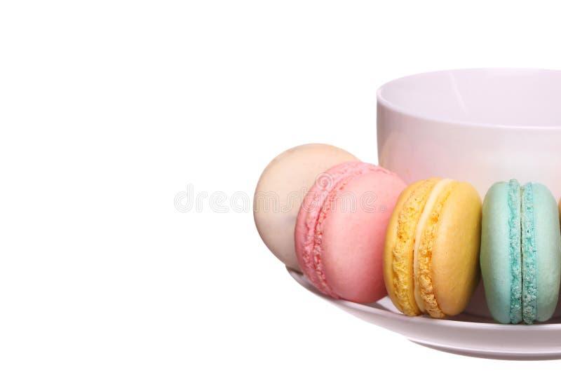 Maccheroni francesi variopinti con la tazza di tè isolata fotografia stock