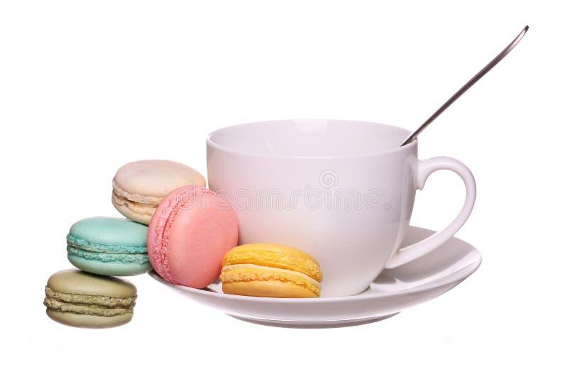 Maccheroni francesi variopinti con la tazza di tè isolata immagine stock