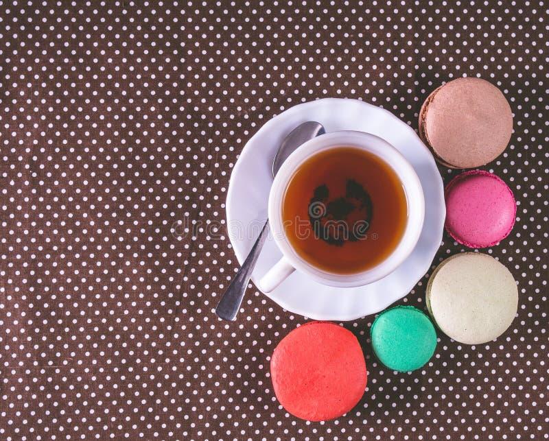 Maccheroni francesi variopinti con la tazza di tè Vista superiore fotografia stock libera da diritti