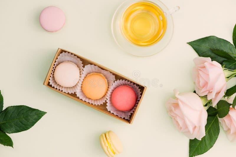 Maccheroni variopinti e fiori rosa con tè su verde chiaro Swe fotografie stock libere da diritti