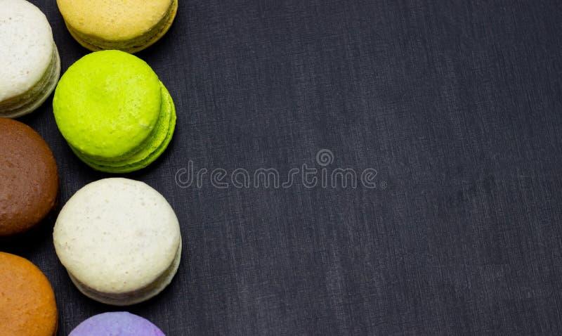 Maccheroni variopinti o dolce dei maccheroni su un fondo scuro Una squisitezza dolce francese immagine stock libera da diritti