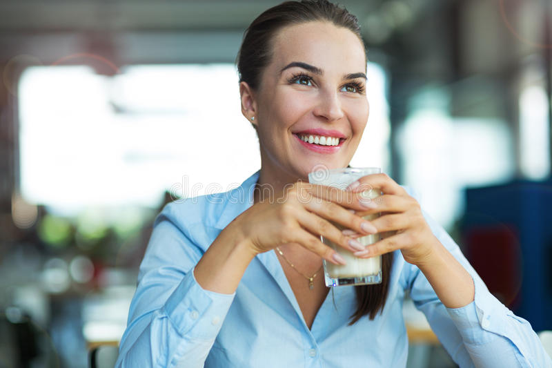 Macchiato bevente del latte della donna al caffè fotografia stock libera da diritti