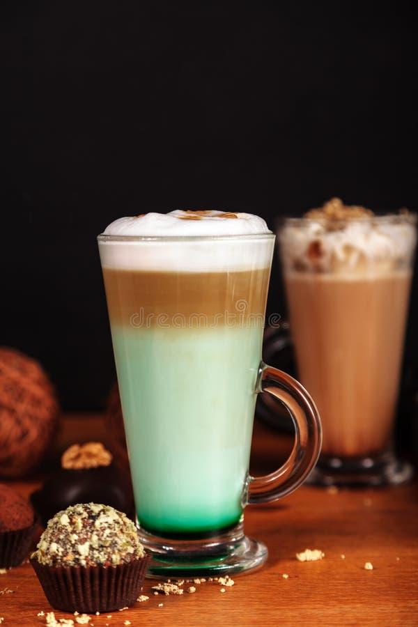 Macchiato del latte del caffè con lo sciroppo della menta e la panna montata, in alti vetri trasparenti con i dolci, su un fondo  fotografie stock