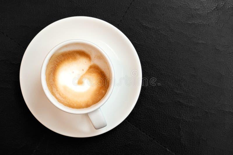 Macchiato do café no copo cerâmico branco com os pires isolados na superfície de couro preta de cima de Espa?o para o texto imagens de stock royalty free