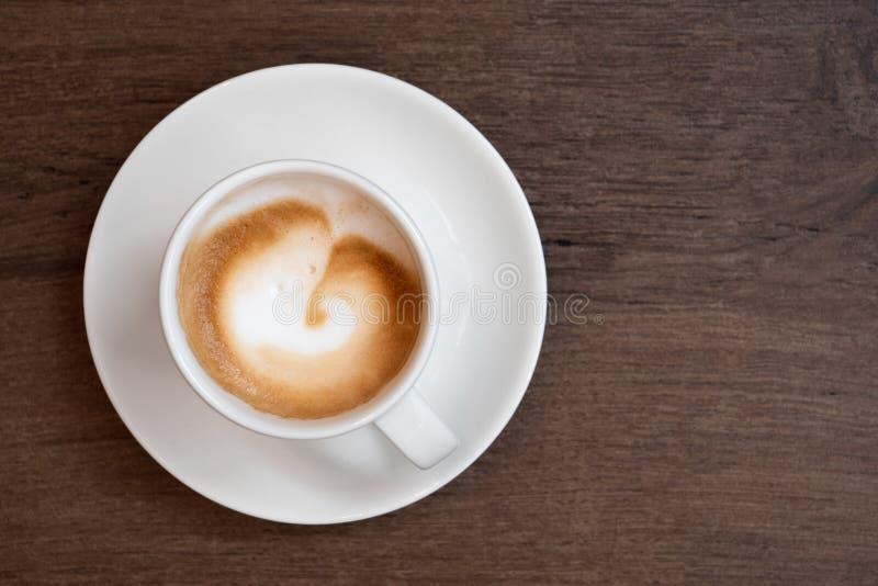 Macchiato do café no copo cerâmico branco com os pires isolados na superfície de madeira marrom de cima de Espa?o para o texto foto de stock royalty free