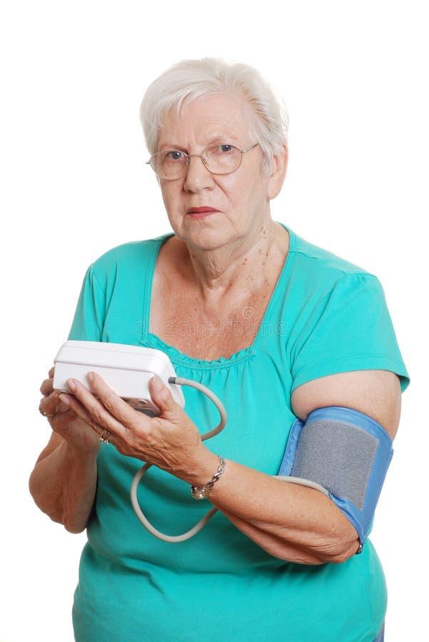 Macchina automatica di pressione sanguigna di uso maggiore della donna immagini stock libere da diritti