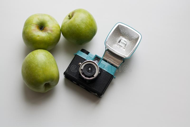 Macchina da presa compatta e tre mele verdi immagini stock libere da diritti