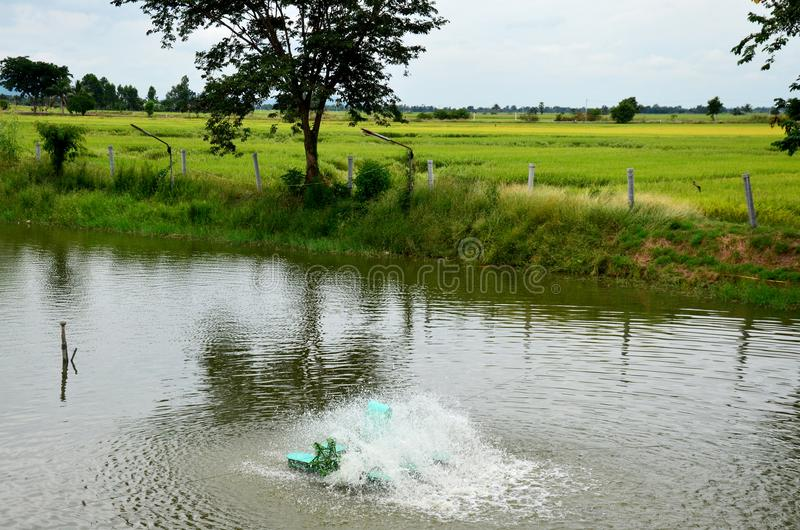 Macchina della turbina dell'acqua in stagno alla campagna immagini stock libere da diritti