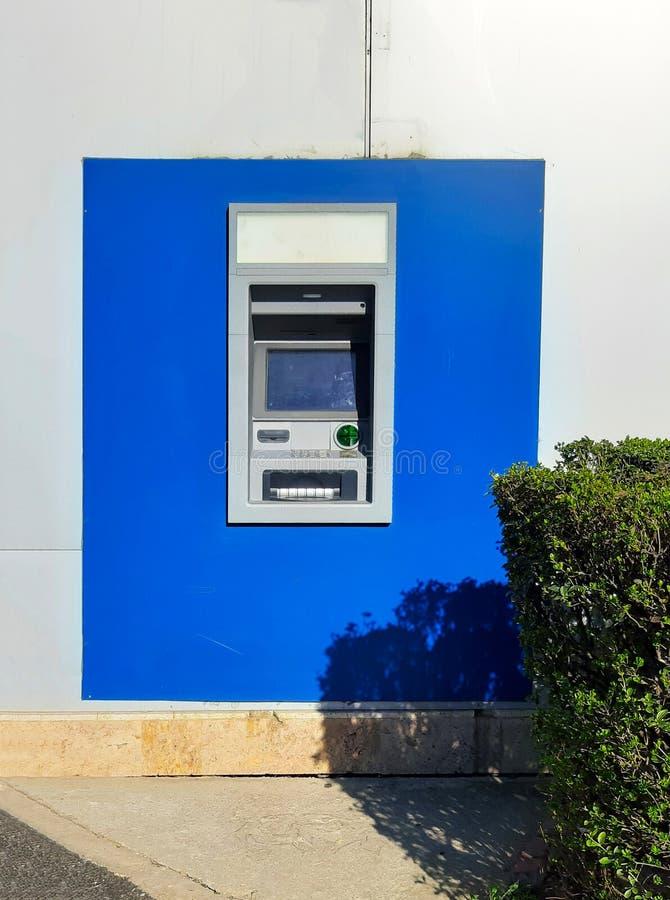 Macchina di BANCOMAT della via per ritiro di soldi e dell'altra transazione finanziaria in parete blu senza gente fotografie stock libere da diritti