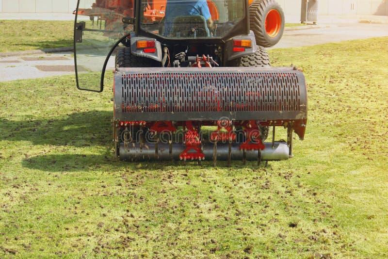 Macchina di Operating Soil Aeration del giardiniere sul prato inglese dell'erba fotografia stock