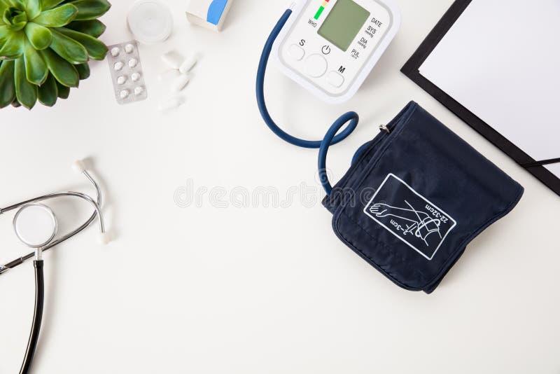 Macchina di pressione sanguigna con lo stetoscopio e la lavagna per appunti su T bianco immagini stock libere da diritti