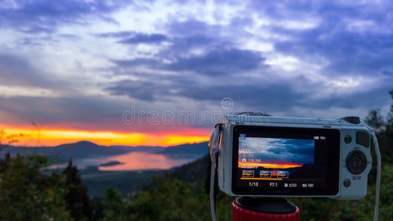 Macchina fotografica che cattura il colpo di tramonto Fotografia utilizzando sul treppiede contro i raggi del sole con la montagn fotografia stock