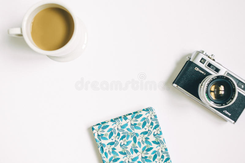 Macchina fotografica con il blocco note ed il caffè