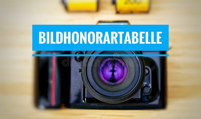 Macchina fotografica con in tedesco Bildhonorartabelle in tavola inglese della tassa dell'immagine fotografie stock libere da diritti