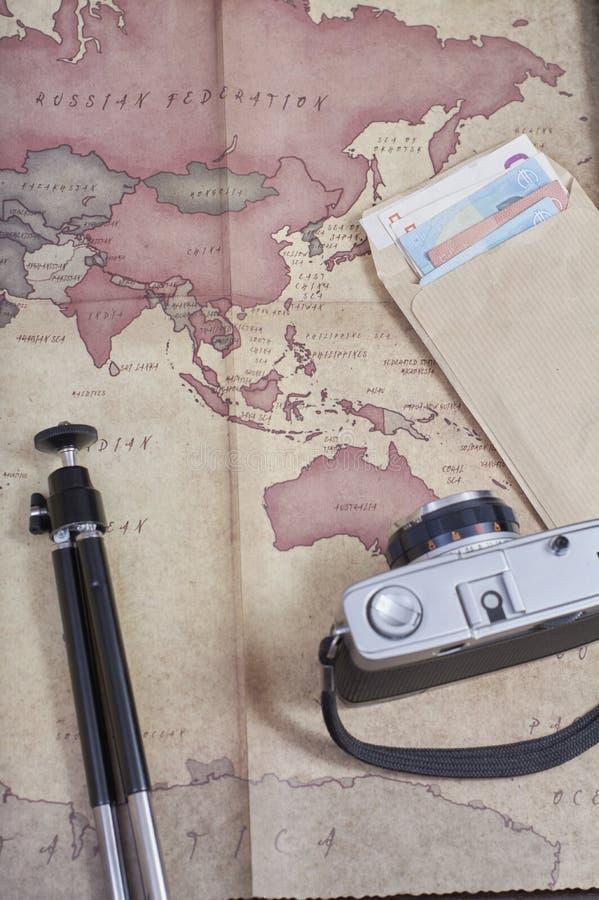 Macchina fotografica d'annata accanto ad una mappa, ad un treppiede e ad una busta di soldi negli euro che preparano un viaggio immagine stock