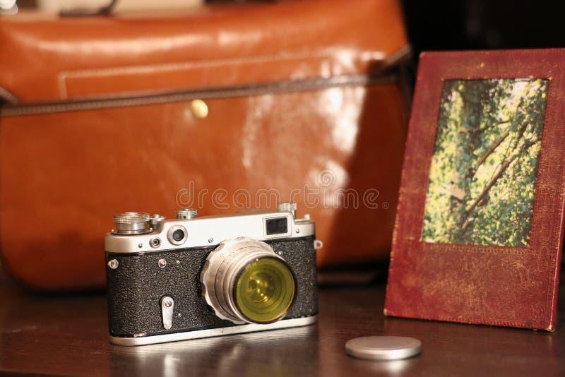 Macchina fotografica d'annata accanto alla borsa per la struttura dell'attrezzatura della foto e della foto immagini stock